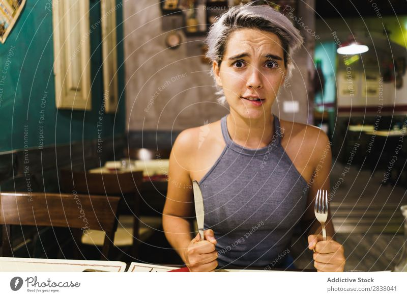 Furious girl posing with silverware Woman Restaurant Appetite having fun Anger Expression facial Emotions humorous hysterical Café Table Adults Stress pretend