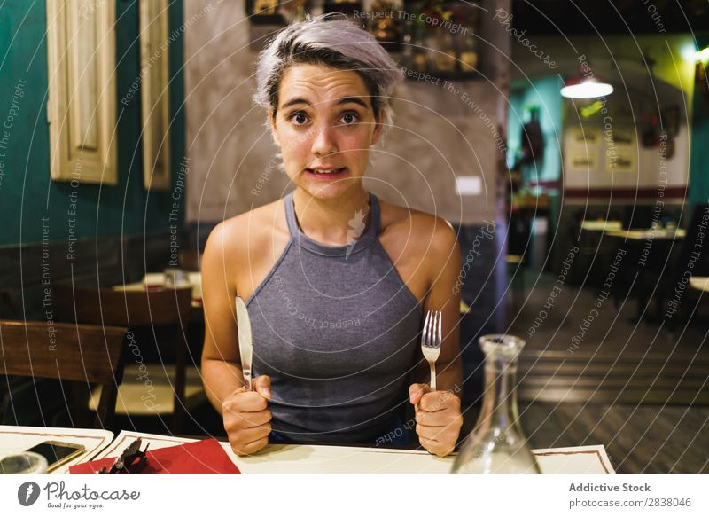 Furious girl posing with silverware Woman Restaurant Appetite having fun Expression facial Emotions humorous hysterical Anger Café Table Adults Stress pretend