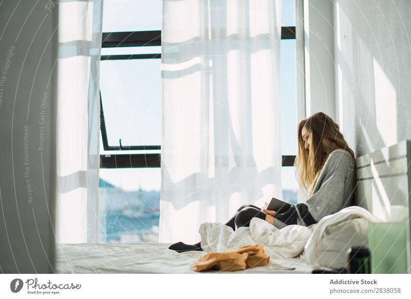 Girl chilling with book in cozy bed Woman Bed Reading Morning Book concentrated Serene Sunlight Peaceful Blonde Safety (feeling of) Home Room Resting To enjoy