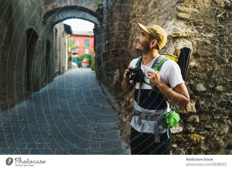 Content traveler enjoying city Man backpacker Street photo camera Old Sightseeing Summer Vacation & Travel Appearance Town Tourist Ancient Vantage point