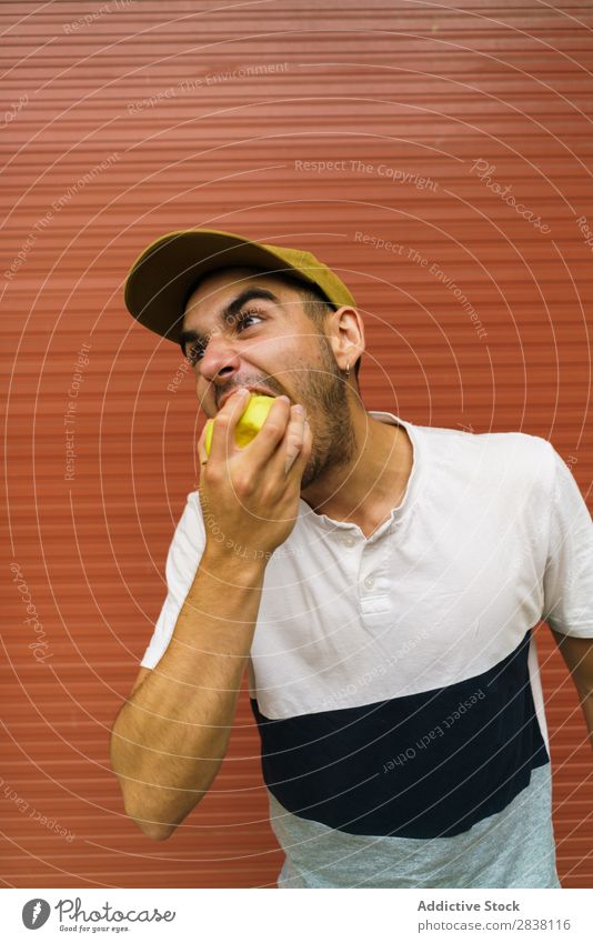 Man eating apple near wall Eating Anger pretend having fun Appetite Expressive Crazy Posture facial Intellect Playful Youth (Young adults) Recklessness