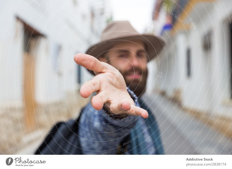 Cheerful bearded man looking at camera and gesturing follow me w Man Tourist Gesture Looking into the camera handsome Smiling Hand Vacation & Travel Tourism Hat