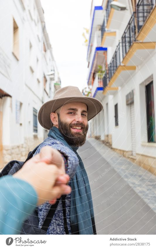 Man holding photographer's hand Tourist follow me Gesture Looking into the camera bearded handsome Smiling Hand gesturing Vacation & Travel Tourism Hat