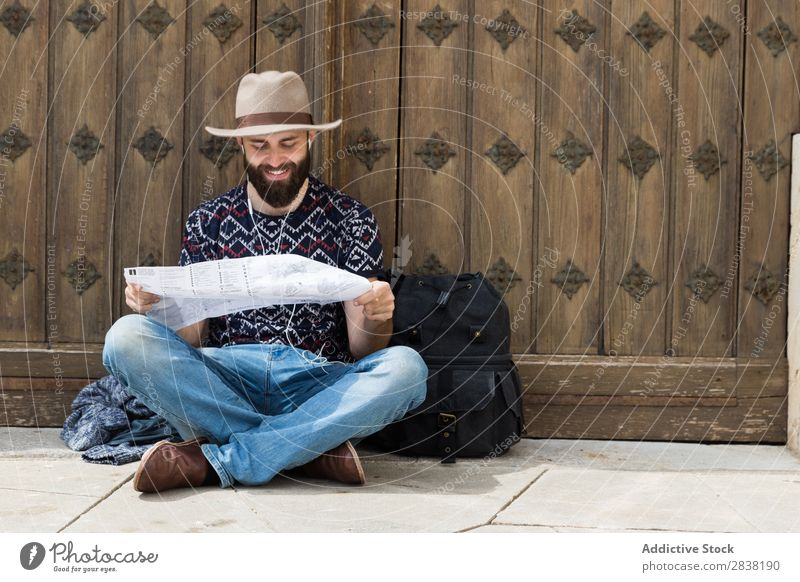 A tourist sitting and reading a map while listening to music Man Headphones Map Backpack Reading Lanes & trails searching Sit Vacation & Travel Tourism Ground