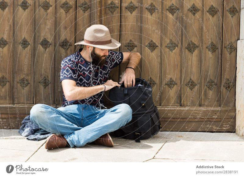Man sitting with headphones and backpack Headphones Backpack searching Sit Vacation & Travel Tourism Ground Portrait photograph Music Youth (Young adults)