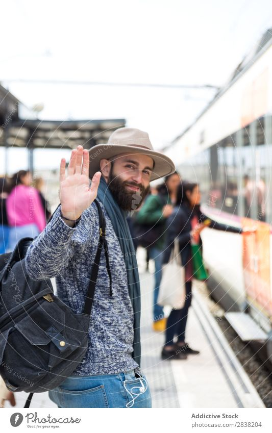 Cheerful tourist on train station Man Tourist Railroad Station Welcome Gesture Goodbye Looking into the camera Vacation & Travel Transport Trip Backpack