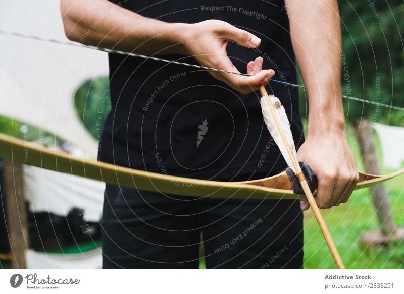 Crop man practicing archery in school Man Archery Aim Concentrate Action Competition Success Fitness Stand challenge focus Exterior shot Bow Arrow Weapon School