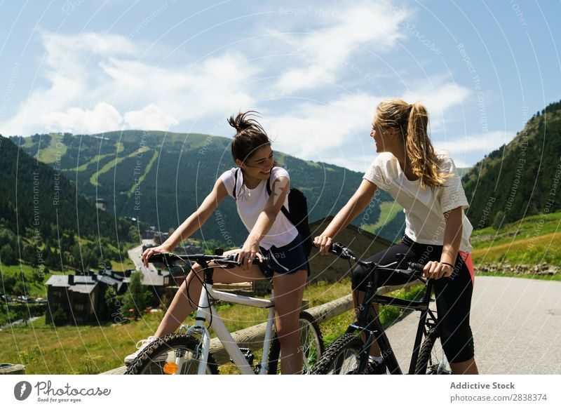 Women riding bikes in countryside Woman Athletic Bicycle Friendship Sports Cycle