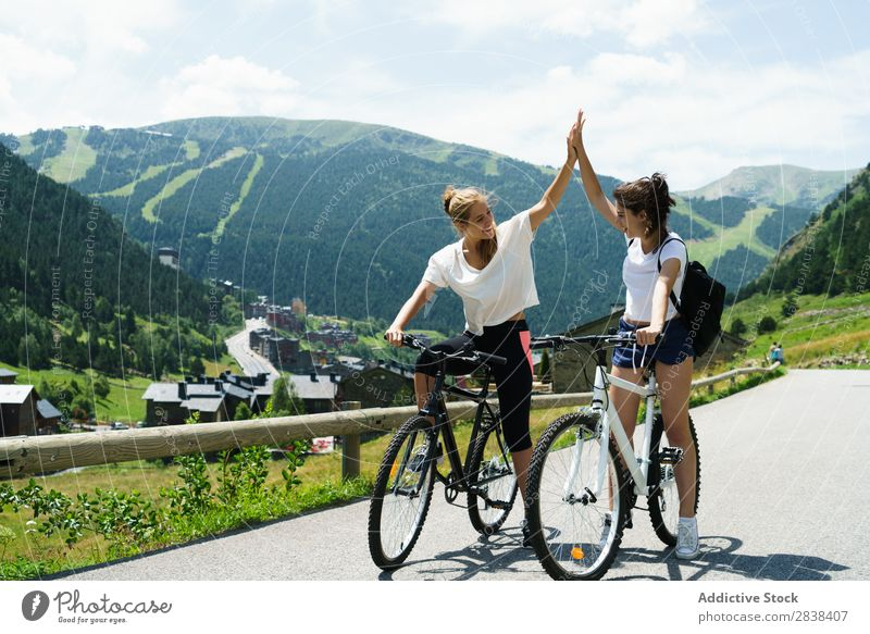 Women on bikes giving high five Woman Athletic Bicycle Smiling Cheerful Team Friendship Sports Cycle Girl Action Lifestyle Cycling Human being workout Mountain