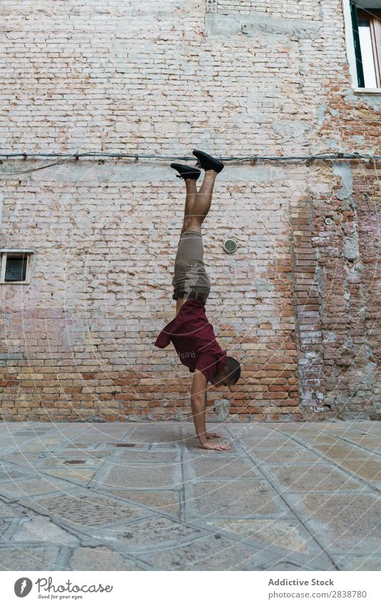 Man performing handstand at old street Handstand Street Town Stand Breakdance Entertainment Athlete Endurance Style Culture Youth (Young adults) Muscular