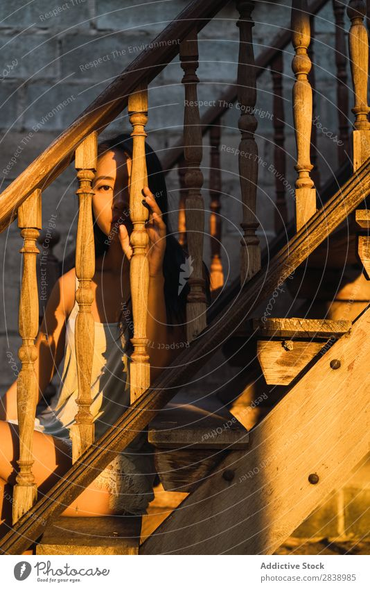 Pensive woman on wooden stairs Woman pretty asian Youth (Young adults) Handrail Wood Steps Evening Sunset Sit Considerate Beautiful Portrait photograph