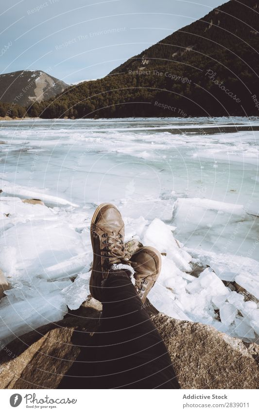 Tourist relaxing at snowy river Human being Legs River Ice Stone Winter Hill Mountain Snow Landscape Nature White Seasons Cold Vacation & Travel Forest Frost