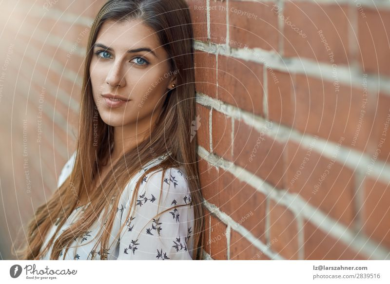 Portrait of young pretty woman near brick wall Lifestyle Joy Happy Beautiful Face Woman Adults 1 Human being 18 - 30 years Youth (Young adults) Nature Autumn