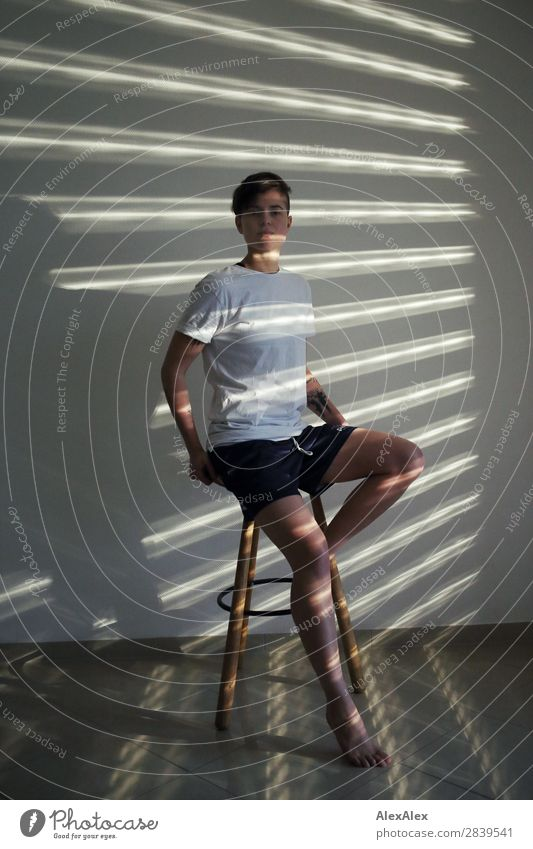Young woman sitting on a stool illuminated in stripes of light Style Beautiful Life Room Stool Strip of light Light and shadow Youth (Young adults)