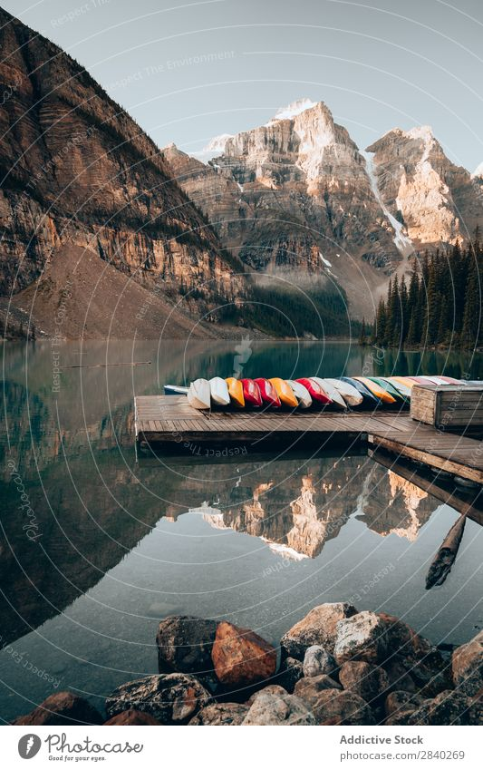 Pier with boats in mountains. Lake Moraine Jetty Watercraft Mountain Reflection Vacation & Travel Tourism Landscape Idyll Calm Transport Vantage point Morning