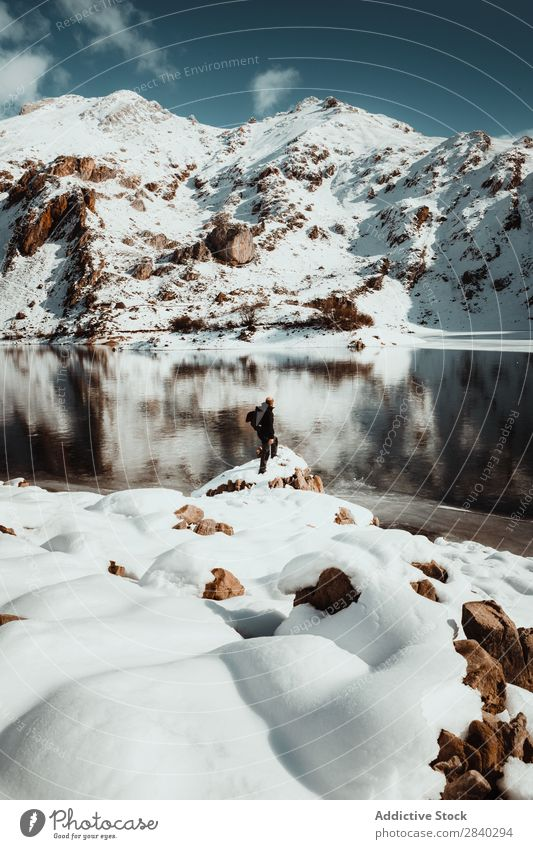 Person on snowy lakeside Human being Lake Mountain traveler Tourism Adventure Snow Reflection Mysterious Rock Landscape Panorama (Format) Nature Wanderlust Sky