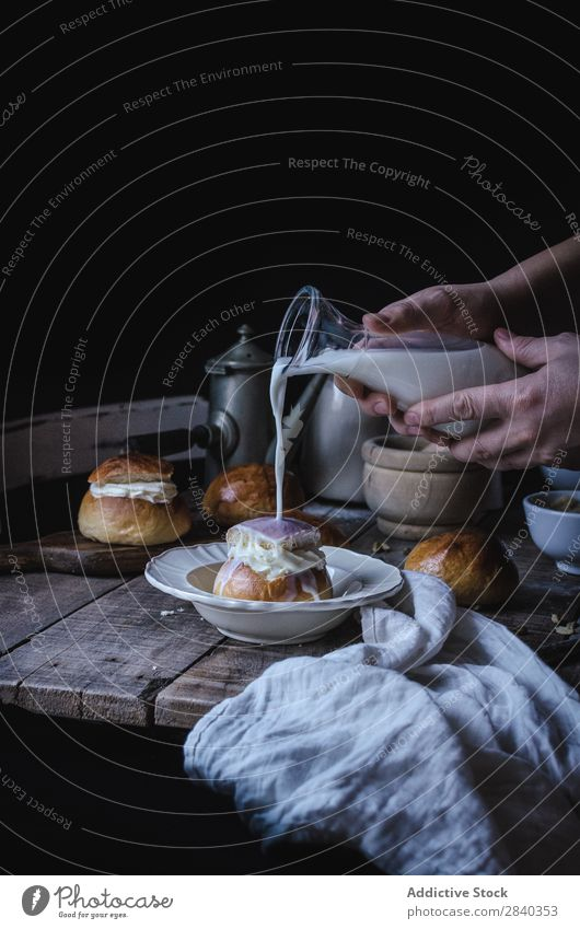Hands pouring milk on bun Sweet Baked goods Rustic Delicious Milk Roll Cream Portion Dessert Food Fresh Tasty Home-made Gourmet Bakery Snack Breakfast Healthy