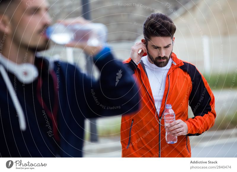 Two young men resting after running in the street. Action Adults Athlete Attractive being Body Considerate Caucasian Practice Athletic Fitness flexibility