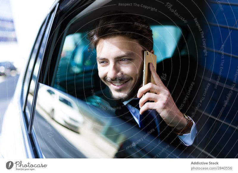 Smiling businessman talking phone in car Man Businessman Car Success Cheerful Work and employment PDA Communication using Internet Adults backseat Successful