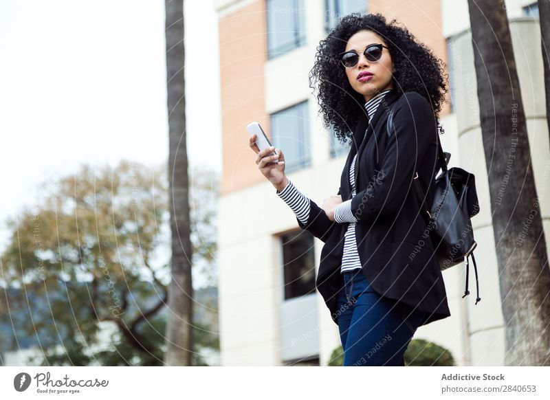 Beautiful woman using her mobile phone in the street. Human being Street Woman Youth (Young adults) Telephone Joy Town texting Internet Cellphone Ethnic