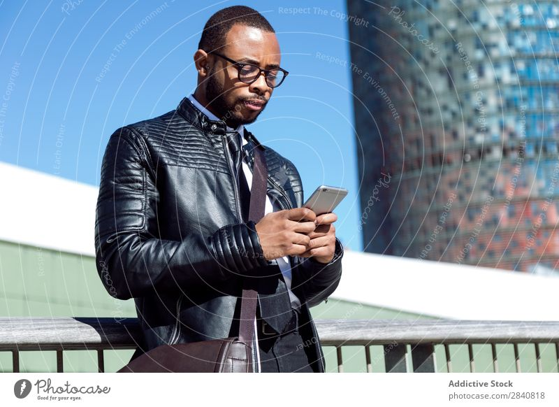 Young male typing on phone Man Successful Telephone Style Self-confident Businessman Technology using browsing Businesspeople African Black handsome Clothing