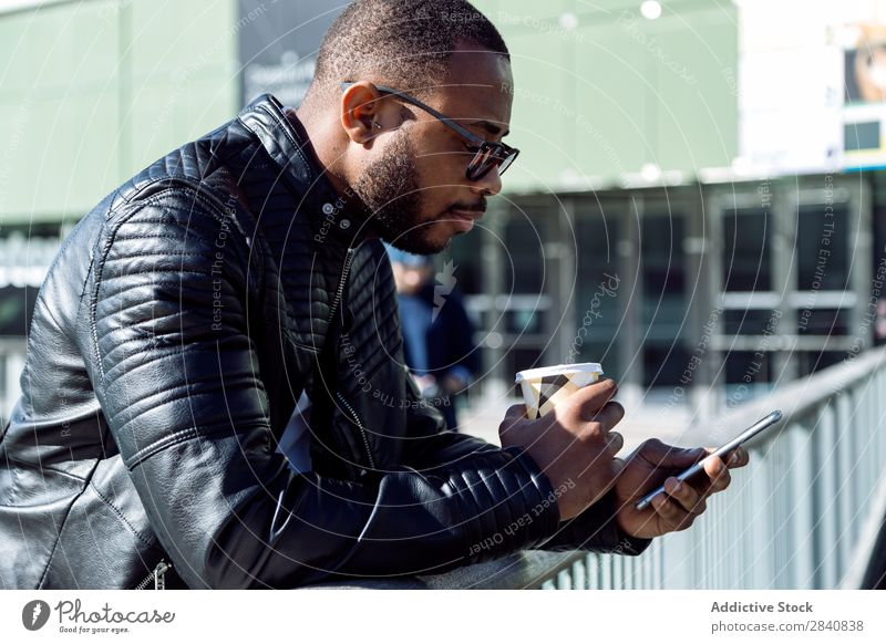 Side view of young man standing with coffee and phone near metal fence. male successful stylish confidence businessman technology morning using browsing manager