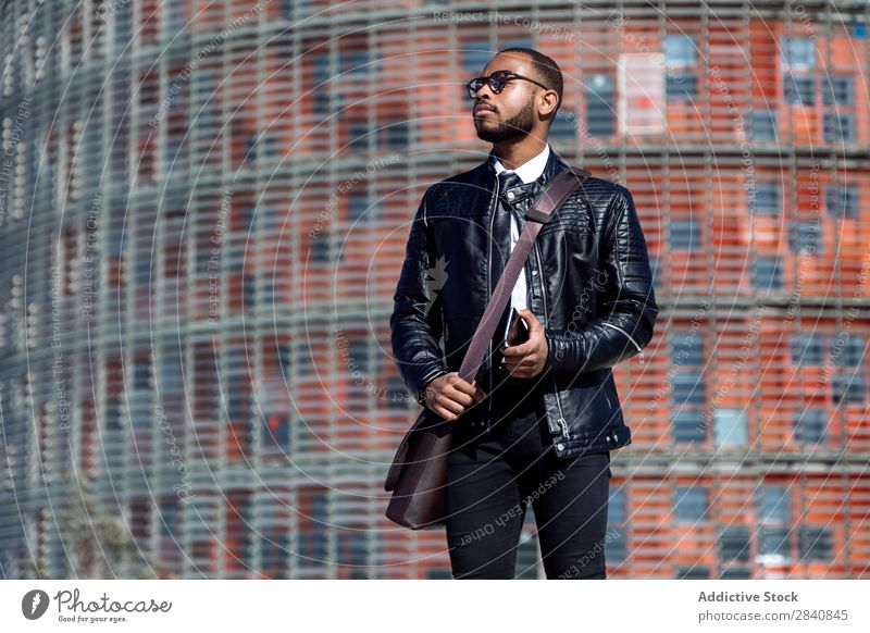 Trendy man in black leather coat and glasses holding smart phone and looking away on urban background. male successful stylish confidence businessman technology