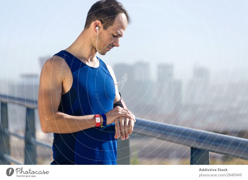Runner man looking at his pulse with smartwatch. Observe Running Sports Time rate Screen Man Fitness cardio workout Healthy sprint Jogging sprinting Marathon