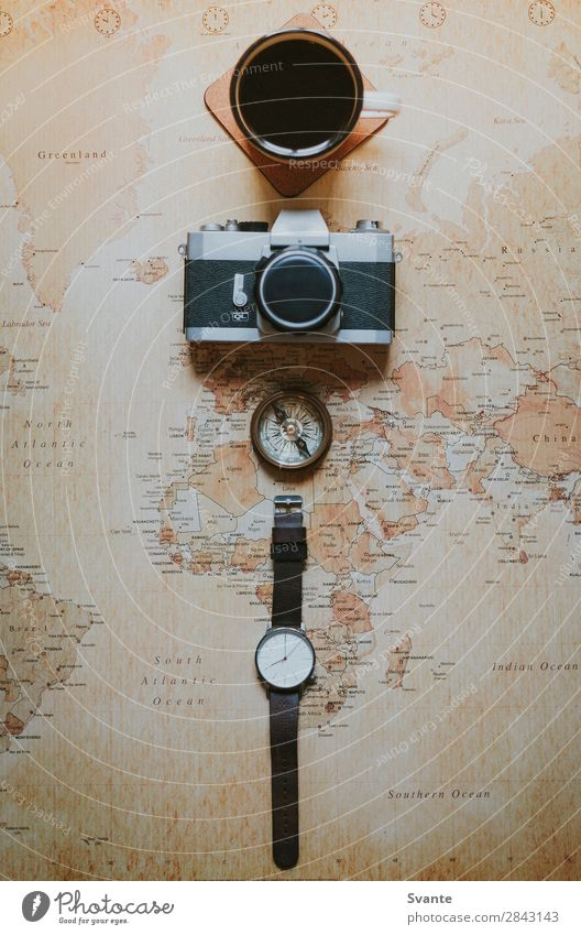 Top view of watch and camera on world map Vacation & Travel Trip Clock Adventure Coffee Planning Beverage Camera Map Tea Cup Analog Expedition Map of the World