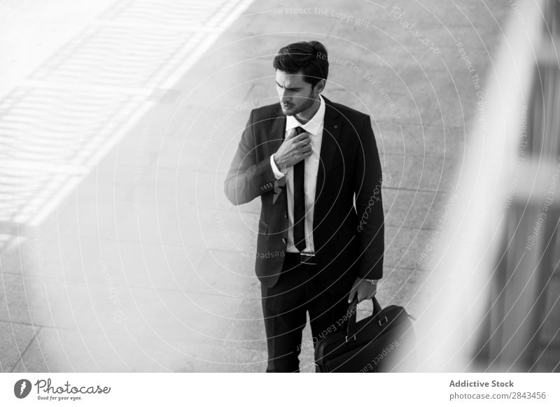 Serious businessman with briefcase holding hand on tie Businessman Street black & white Earnest Portrait photograph Looking away Hold Hand Tie Pensive Stand