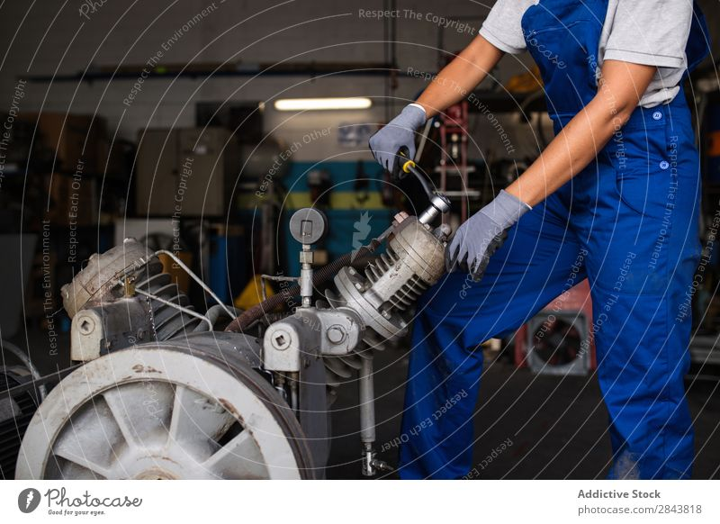 female mechanic fixing a compressor enginge using a wrench Mechanic Woman Portrait photograph Repair Employees & Colleagues Industrial Engines Technology