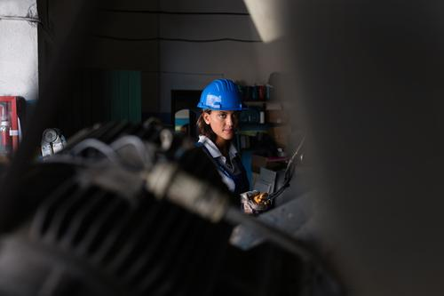 Female mechanic operating a hoist to lift a compressor engine Mechanic Woman Repair Employees & Colleagues Industrial safety helmet Engines Lift Maintenance