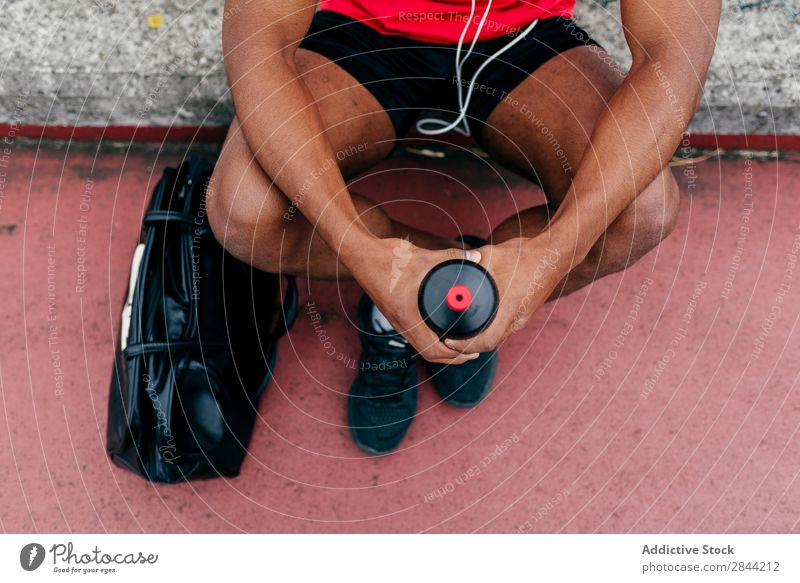 Content sportsman after workout posing outdoors Man Athletic Music Relaxation Posture PDA Technology Action motivation Headphones Cheerful Bag