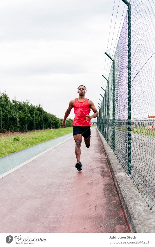 Man running along fence Jogging Track Running Town sportsman Healthy workout Action Speed in motion Nature Practice Athletic Wellness Black