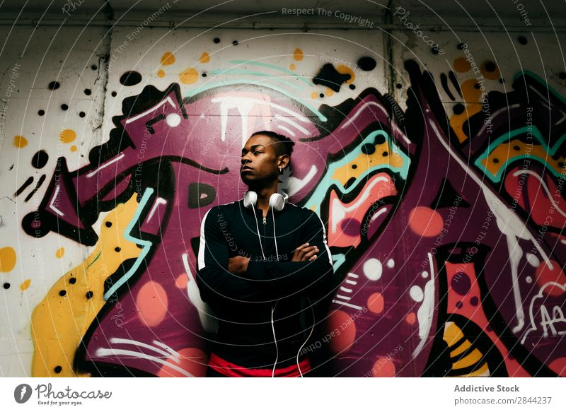 Confident man posing against graffiti Man Posture Uniqueness Graffiti Style Independence Self-confident Black Headphones City Technology hands crossed Easygoing