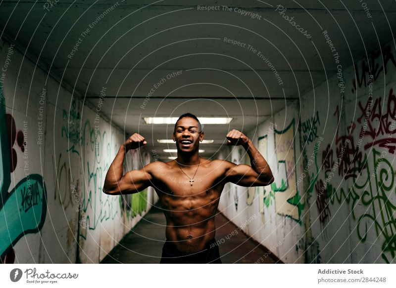 Cheerful sportsman posing underground Man grungy Athletic Musculature Indicate shirtless Sports African Graffiti Underground handsome Torso Model Body Posture