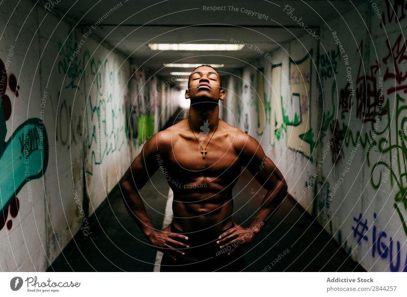 Cheerful sportsman posing underground Man grungy Athletic Musculature Indicate shirtless Sports African Graffiti Underground handsome Torso Model Body Posture