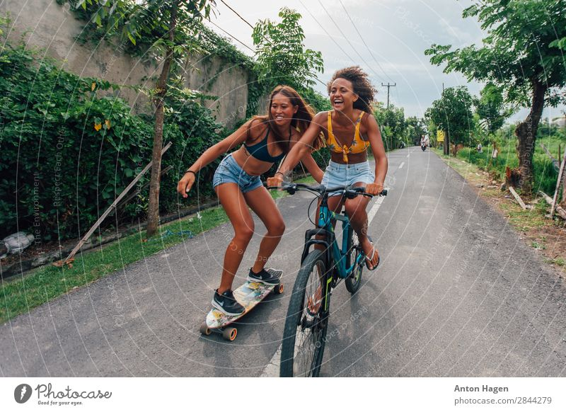 Two young woman riding bicycle and skateboard Lifestyle Sports Fitness Sports Training Bicycle Human being Feminine Young woman Youth (Young adults) 2