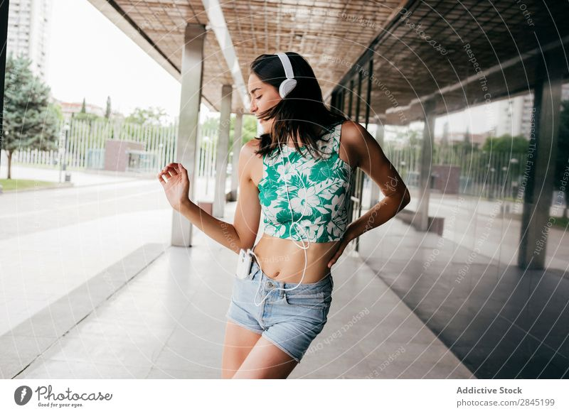 Pretty woman dancing in headphones Woman Music PDA Dance Headphones Street City Town Girl Youth (Young adults) Telephone Lifestyle Beautiful Technology Happy