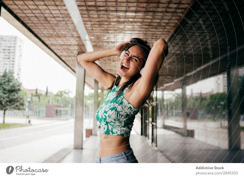 Expressive woman dancing in headphones Woman Music Dance Excitement Headphones Street City Town Girl Youth (Young adults) Telephone Lifestyle Beautiful