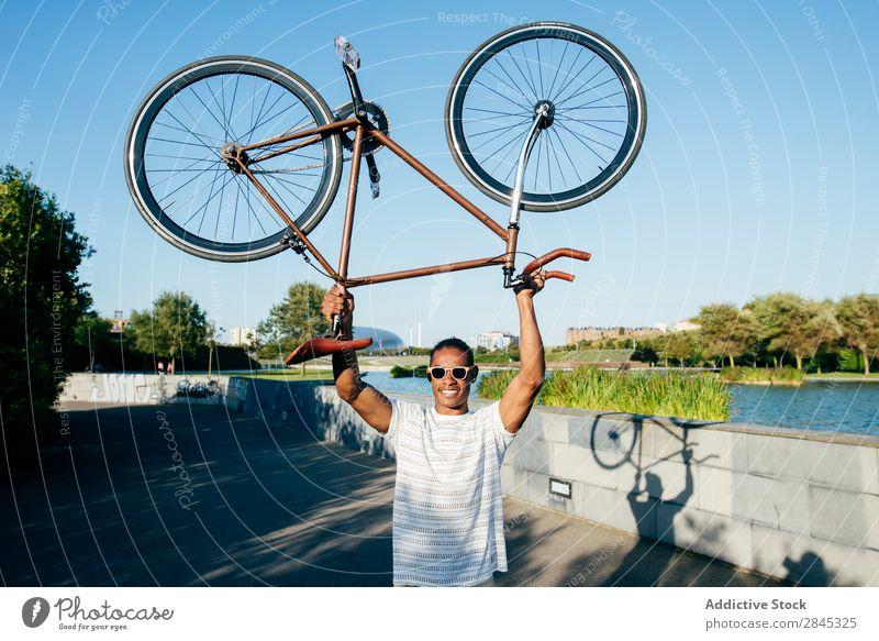 Cheerful man holding bicycle Man Bicycle Hold over head Youth (Young adults) Black Easygoing Stand City Human being Lifestyle Athletic Sports Cycling Posture