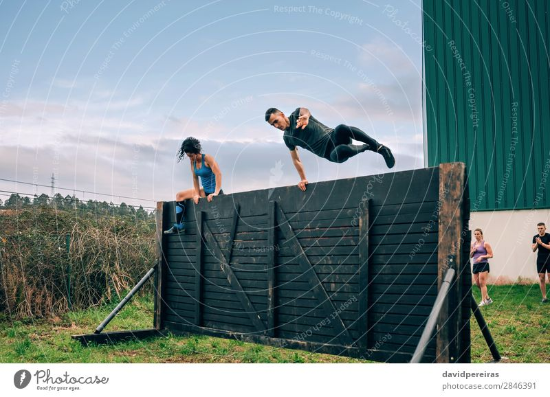 Participants in obstacle course climbing wall Lifestyle Sports Climbing Mountaineering Human being Woman Adults Man Group Jump Authentic Strong Effort Energy