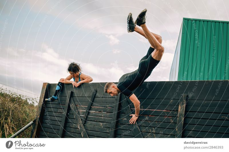 Participants in obstacle course climbing wall Lifestyle Sports Climbing Mountaineering Human being Woman Adults Man Jump Authentic Strong Effort Energy