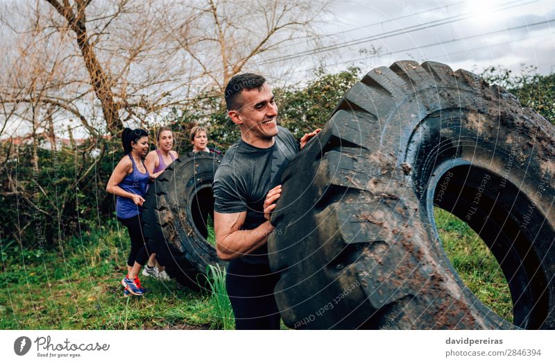 Participant in an obstacle course turning wheel Sports Human being Woman Adults Man Group Smiling Authentic Strong Power Effort Competition Teamwork truck wheel