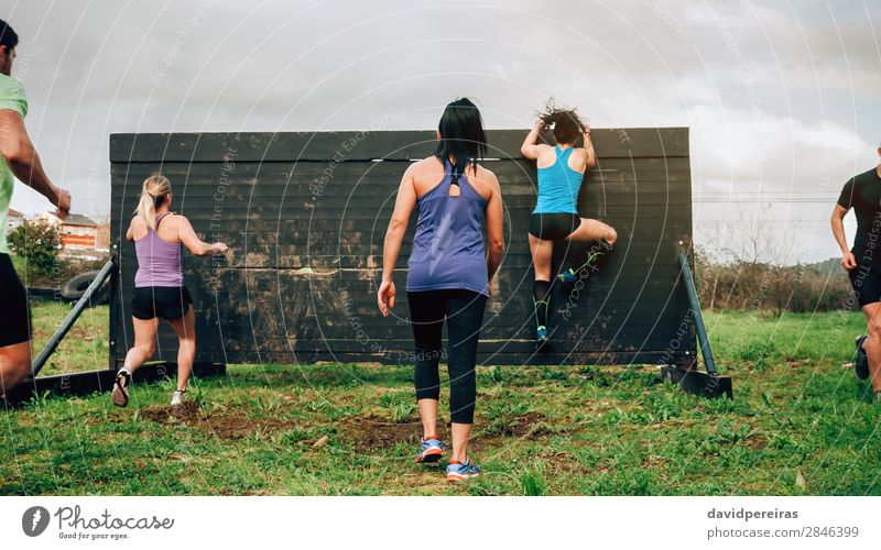 Participants in obstacle course climbing wall Lifestyle Sports Climbing Mountaineering Human being Woman Adults Man Group Jump Authentic Strong Effort