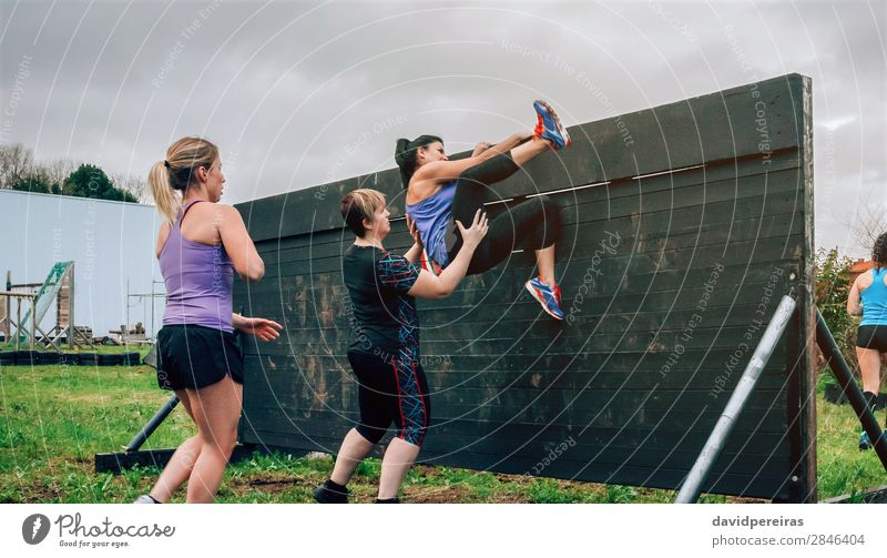 Female participants in obstacle course climbing wall Lifestyle Sports Climbing Mountaineering Human being Woman Adults Group Authentic Strong Effort Competition
