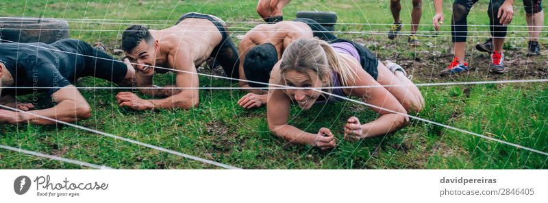 Participants in an obstacle course crawling Joy Happy Sports Internet Human being Woman Adults Man Group Dirty Black Effort Competition Barbed wire