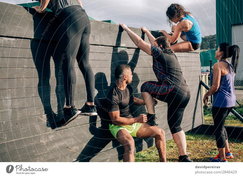 Participants in obstacle course climbing wall Lifestyle Sports Climbing Mountaineering Human being Woman Adults Man Group Authentic Black Effort Competition