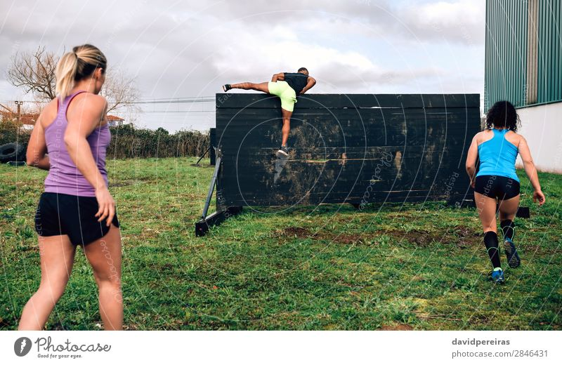 Participants in obstacle course climbing wall Lifestyle Sports Climbing Mountaineering Human being Woman Adults Man Group Jump Authentic Strong Black Effort