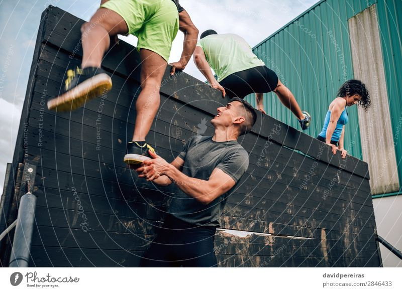 Participants in obstacle course climbing wall Sports Climbing Mountaineering Human being Woman Adults Man Feet Group Authentic Strong Black Effort Competition